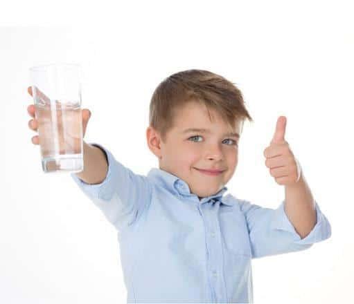 Niño con pulgar levantado y vaso de agua